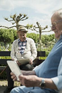Germany, Worms, Two old men using tablet computers in the park - UUF000701