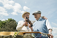 Two old friends toasting with beer bottles in the park - UUF000709