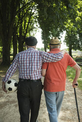 Two old friends walking in the park with football, back view - UUF000713