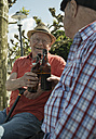 Two old friends toasting with beer bottles in the park - UUF000725