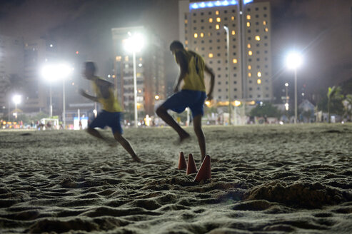 Brazil, Fortaleza, Beach Praia de Iracema, Teenagers playing football at night - FLK000283