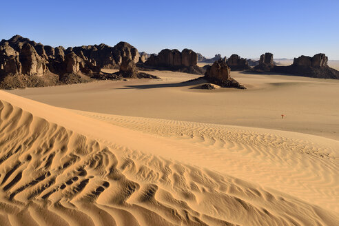 Africa, Algeria, Sahara, Tassili N'Ajjer National Park, Sand dunes and rock formations at Tikobaouine, One woman standing in desert - ES001177