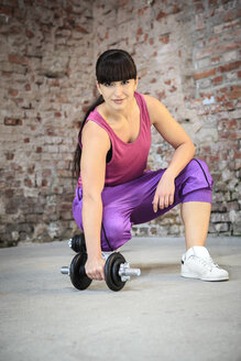 Woman with barbells doing fitness exercise in a gym - VTF000269