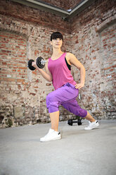 Woman with barbells doing fitness exercise in a gym - VTF000266