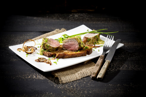 Fillet of pork on crusty bread with mustard herb butter and rucola on plate - MAEF008369