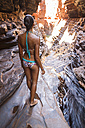 Australia, Western Australia, Karijini National Park, Hancock Gorge, woman standing at canyon, back view - MBEF001018