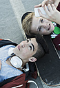Two boys with cell phone and headphones lying on ground - UUF000803