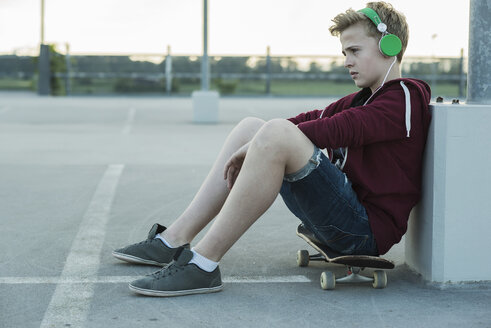 Serious teenage boy outdoors on skateboard listening to music - UUF000815