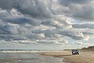 Australia, New South Wales, Pottsville, off-road vehicle standing on beach with surf and dark clouds - SHF001402