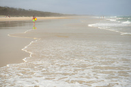 Australia, New South Wales, Pottsville, misty beach with breakwater and a surfer walking in the distance - SHF001394