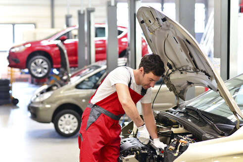 Car mechanic in a workshop working at car - LYF000043