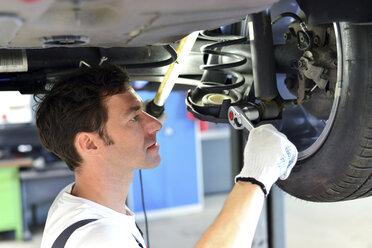 Car mechanic in a workshop working at car - LYF000049