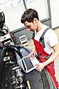 Car mechanic in a workshop using modern diagnostic equipment - LYF000051