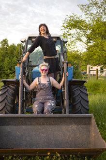Germany, Brandenburg, Bienenwerder, portrait of two female farmers on tractor - FX000005