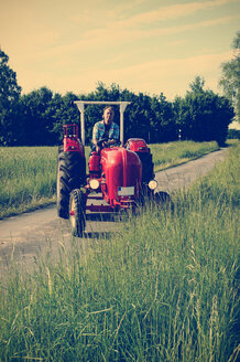 Germany, North Rhine-Westphalia, Minden, Oldtimer Porsche, Man driving an old tractor - HOHF000869
