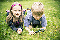 Brother and sister lying on meadow watching flowers with magnifying glass - SARF000673