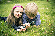 Brother and sister lying on meadow watching flower with magnifying glass - SARF000676