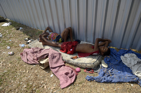 Brazil, Rio de Janeiro, two street children sleeping on mattress in front of hoarding in the city center - FLK000326