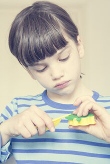 Portrait of little girl with cutter and green modeling clay - LVF001413