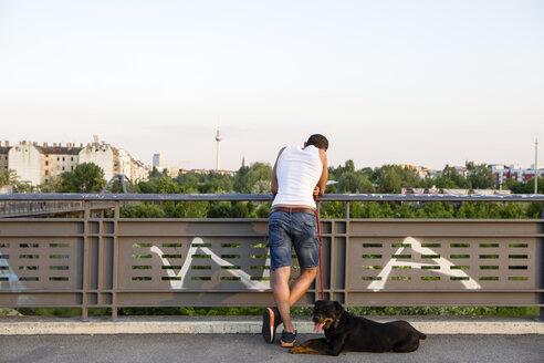Germany, Berlin, young man with Rottweiler resting on pedestrian bridge - FX000015
