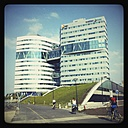 The Netherlands, North Holland, Amsterdam, Modern office building in Amsterdam with people on bicycles passing by, - HAW000271