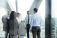 Businesspeople in office with woman using digital tablet - WEST019276