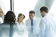 Businesspeople in office with woman using digital tablet - WEST019279