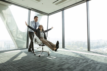 Businessman pushing businesswoman in office chair - WESTF019494