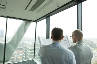 Two businessmen in office looking at blueprint - WESTF019371