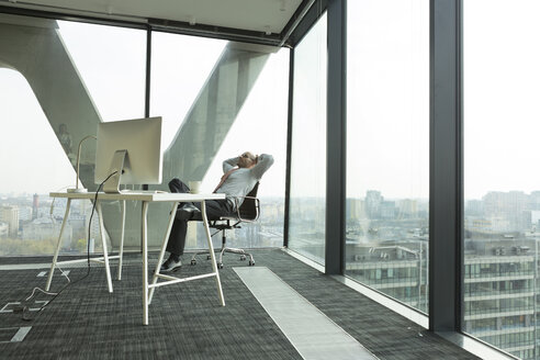 Businessman leaning back in new office - WESTF019507