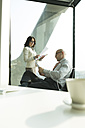 Businessman and businesswoman with documents in office - WESTF019294