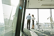 Businessman and businesswoman talking in office - WESTF019514