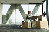 Businesswoman using laptop with feet on cardboard boxes - WESTF019304