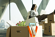 Cardboard box on office floor with businesswoman in background - WESTF019306