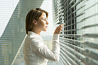 Businesswoman looking through blinds - WESTF019377