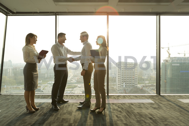 Two businessmen in sunny office shaking hands - WESTF019390
