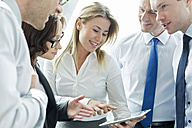 Businesspeople in office with woman using digital tablet - WEST019436