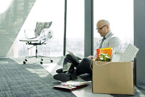 Businessman using laptop on empty office floor with cardboard box - WESTF019367