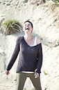 Portrait of laughing woman in front of sand dune - MAE008398