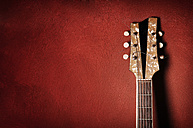 Guitar leaning against red wall - IPF000124