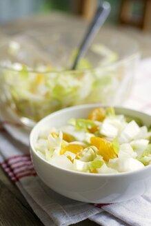 Bowls of Belgian endive salad with mandarin oranges on kitchen towel - HAWF000283