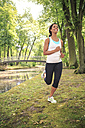 Geramny, Bavaria, Bayreuth, Woman jogging by a river in the city park - VTF000282