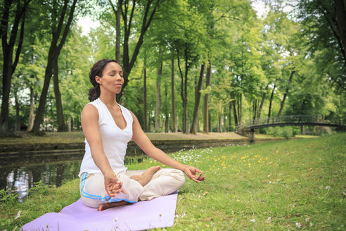 Germany, Woman exercising yoga in a park, Meditation - VTF000279