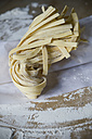 Fresh unwrought tagliatelle and flouron baking paper - ASF005420