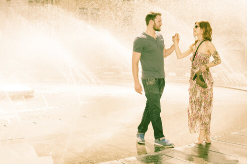 Germany, Bavaria, Munich, young couple in love standing hand in hand in front of fountain at Stachus - FCF000234