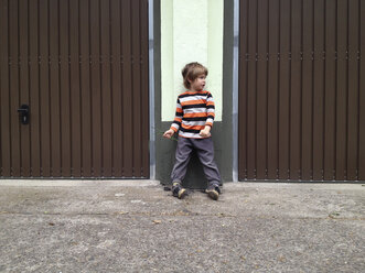 Child is standing on feet kippelnd between two garage doors. Berlin, Germany - ZMF000302