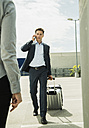 Business man with rolling suitcase telephoning with smartphone - UUF000896