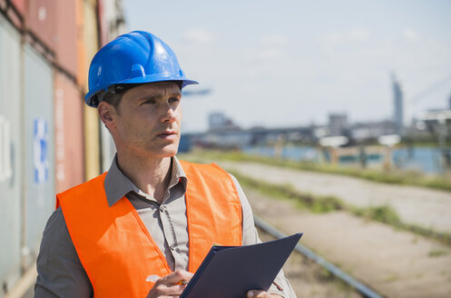 Portrait of man with blue safety helmet checking cargo containers - UUF000938