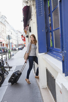 France, Paris, portrait of young woman with rolling suitcase arriving at hotel - FMKF001246