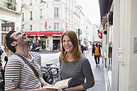 France, Paris, portrait of happy couple exploring the city with travel guide - FMKF001249